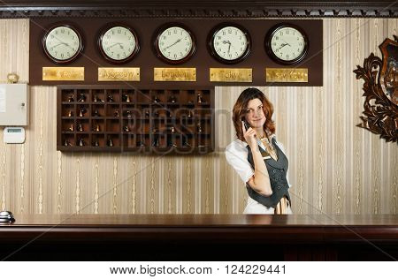 Hotel reception. Female receptionist at reception. Modern hotel reception counter desk with bell taking a call. Woman receptionist, concierge with phone. Travel, hospitality, hotel booking concept.