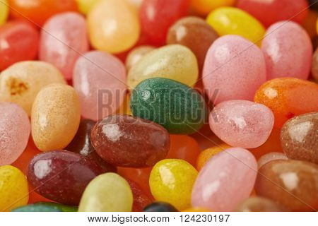 Surface covered with multiple colorful jelly bean candies as a backdrop composition