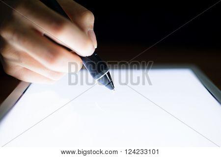 Woman using digital pen on tablet pc