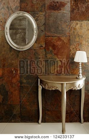 Stylish interior with mirror and dressing table front of rusty metal surface.