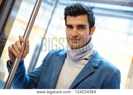 Portrait of handsome young man standing in entrance.
