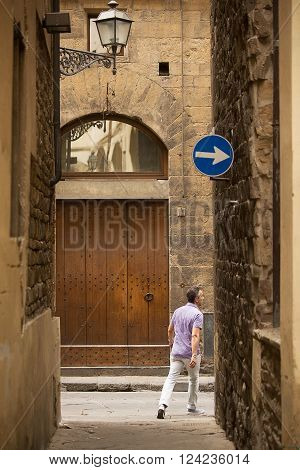 Florence-Italy, June 12, 2015. View down one of the ancient alleys that criss cross Forence, Italy, with locals and tourists.
