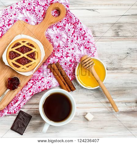 Mini tart with jam, honey, cinnamon sticks, sugar cubes and a cup of coffee on the wooden table, selective focus