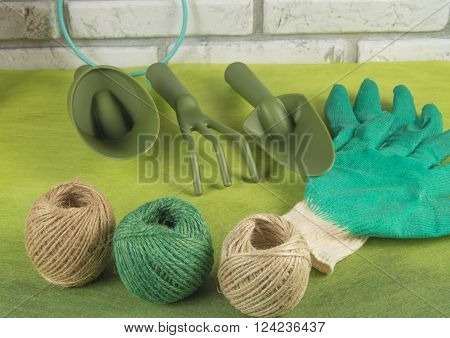 Garden tools, working gloves and balls of twine on a green background