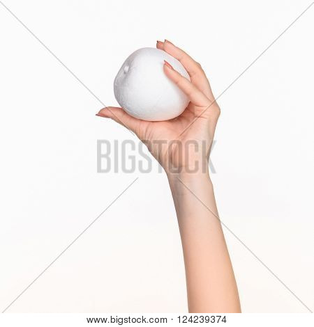 The female hand holding white blank styrofoam oval against the white background  with right shadow