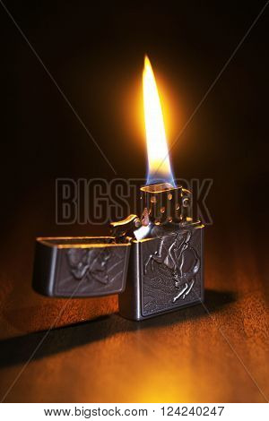 Beautiful lighter on a wooden floor igniting the dark room