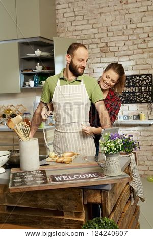 Happy couple in kitchen, woman tieing apron on man.