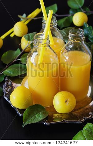 Natural plum juice in a bottle of yellow plums on a black wooden background. Bio healthy food and drink concept. Selective focus