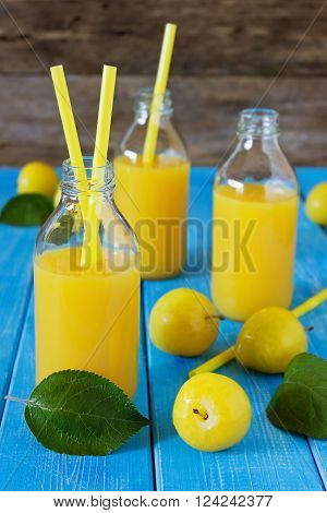 Natural plum juice in a bottle of yellow plums on a blue wooden background. Bio healthy food and drink. Selective focus