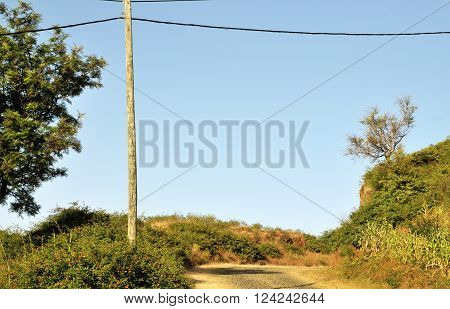 Electric utility pole and wire cross over a cobblestone road on the remote mountain top town of Monte Preto on the island of Fogo, Cabo Verde