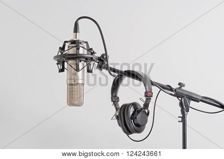 Professional condenser microphone with headphones on a stand. White background.