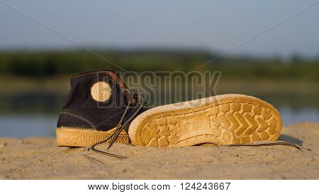 A pair of sports gym shoes on a sand