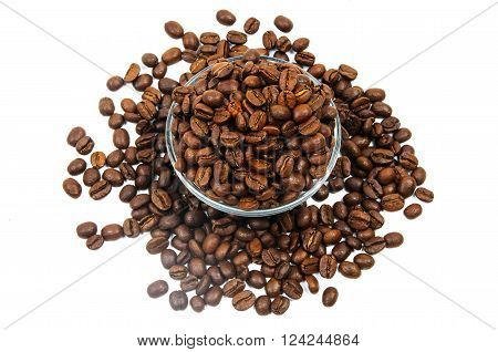 Scattered brown coffee beans inside and around glass jug