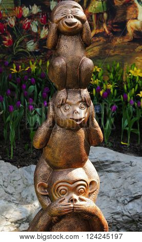 Three monkey statues representing see no evil hear no evil and speak no evil within a greenhouse at Chenshan Botanical Garden Shanghai China.