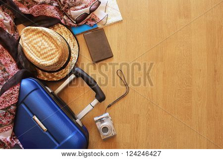 Suitcase and tourist stuff on wooden background