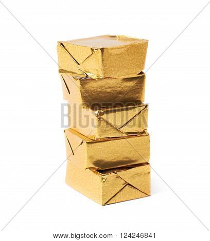 Stack of mulitple bouillon stock broth cubes wrapped in golden foil, composition isolated over the white background ** Note: Shallow depth of field
