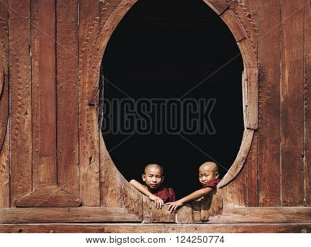 Nyaung Shwe, Myanmar - March 24, 2014: Novice Buddhist monks sitting by the window at Shwe Yan Pyay Monastery in Nyaung Shwe village near Inle Lake, Shan State, Myanmar (Burma).