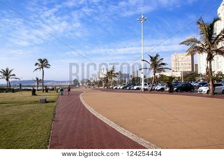 DURBAN SOUTH AFRICA : APRIL 1 2016: Many unknown people on early morning beach front against city skyline in Durban South Africa