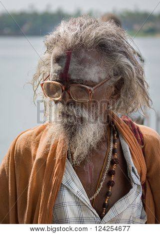 Trichy India - October 15 2013: Old graying sadhu with beard and glasses. Wears orange garb and has his forehead smeared with white and red. Seen in Anna Mandapam.