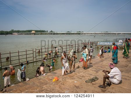Trichy, India - October 15, 2013: Ritual bathing in Cauvery River at Amma Mandapam. Wide view on river and the ghat. Fence to protect bathers from current.