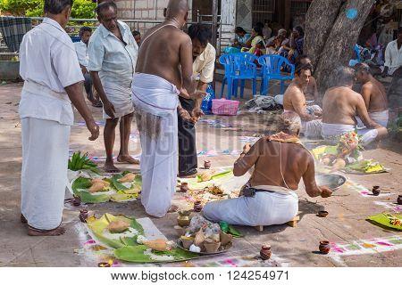 Trichy, India - October 15, 2013: Men prepare mandala for ritual at Amma Mandapam. Sitting guru leads the ritual. Plenty of offerings in the square.