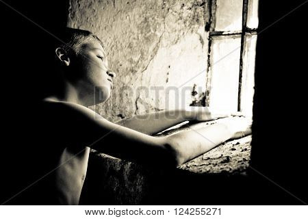 Black and white view on single poor shirtless male child near glass block window in dirty room