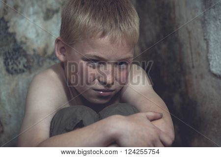Weeping abused or imprisoned blond boy curled up with arms around knees in corner of stone walled jail cell