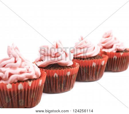 Chocolate muffin coated with the pink cream frosting, composition isolated over the white background, close-up crop fragment