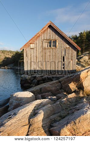 Old boathouse standing betwen the water on stone and in the sunshine