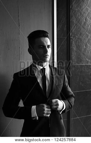 Man Buttons Suit Coat