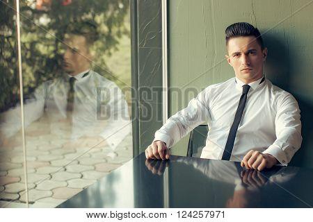 Man Model Sits At Table