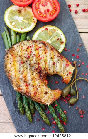 A sturgeon steak served with asparagus lemon tomatoes capers and spices