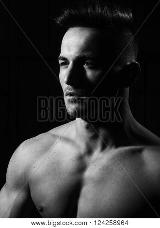 Sensual upper half portrait of strong athletic young hot macho man with fashion haircut looking away with powerful muscular bare shoulders posing on dark background closeup studio black and white