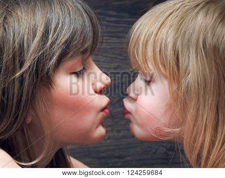 Two sisters - one older and one younger, girlfriend. Girls are very similar to each other. Face close. Blondes. Relationships in the family children. Kiss nurses