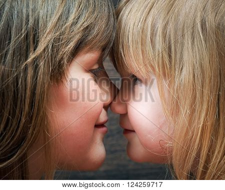 Two sisters - one older and one younger, girlfriend. Girls are very similar to each other. Face close. Blondes. Relationships in the family children