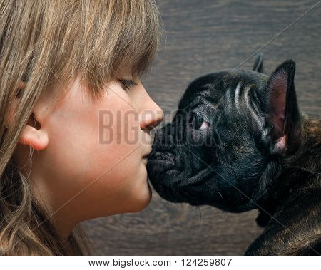 Kiss Dog and child. The girl's face and large dog muzzle. Concept - the relationship of man and dog. Dog black French bulldog. Girl teenager with blond hair