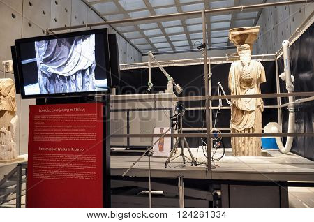 ATHENS, GREECE - JANUARY 28, 2011: Media press presentation of restoration and conservation work on the Caryatids at the New Acropolis Museum. Laser equipment on platform to remove surface contamination.