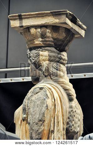 ATHENS GREECE - JANUARY 28 2011: Media press presentation of restoration and conservation work on the Caryatids at the New Acropolis Museum. Conservator using laser to remove surface contamination. Partially completed side view.