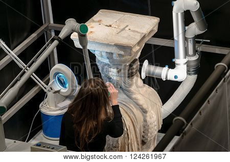 ATHENS GREECE - JANUARY 28 2011: Media press presentation of restoration and conservation work on the Caryatids at the New Acropolis Museum. Conservator using laser to remove surface contamination.
