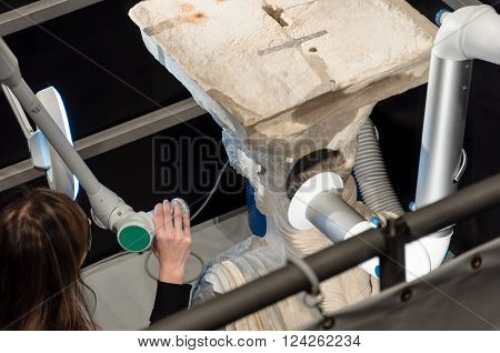 ATHENS, GREECE - JANUARY 28, 2011: Media press presentation of restoration and conservation work on the Caryatids at the New Acropolis Museum. Conservator using laser to remove surface contamination.