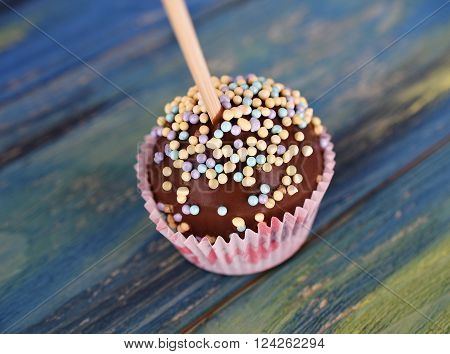 Mini cake on a stick. Chocolate POPCAKE at wrapper on blue wooden background
