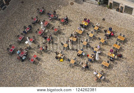 People Sitting At Outdoors Cafe On The Square
