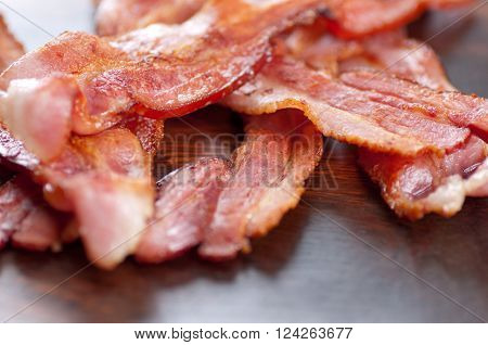 crispy sliced ethically raised organic bacon on a wooden plate