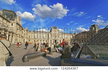 PARIS FRANCE - MAY 3 2012: Louvre Pyramid and Louvre Palace crowded with tourists in Paris in France. Palace of Louvre now is a museum. Louvre Pyramid is a large metal and glass pyramid