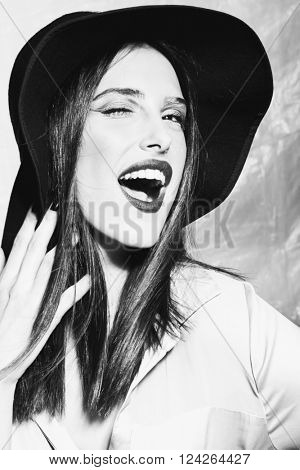 smiling beautiful young woman with hat wink portrait in studio black and white