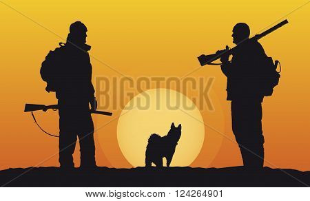 Silhouettes of hunters with dog at sunset background