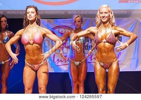 MAASTRICHT THE NETHERLANDS - OCTOBER 25 2015: Female fitness bikini models show their best front pose at championship on stageat the World Grandprix Bodybuilding and Fitness of the WBBF-WFF on October 25 2015 at the MECC Theatre in Maastricht