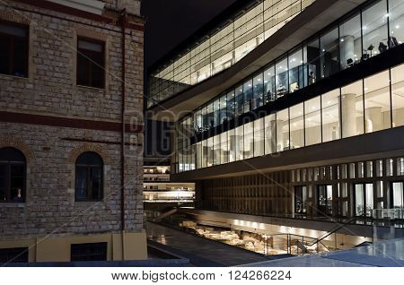 ATHENS GREECE - JANUARY 28 2011: Aspect of the New Acropolis Museum exterior next to the Wilhelm von Weiler building at night