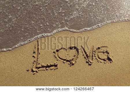 Word love handwriten in golden sand on the beach next to the waterline