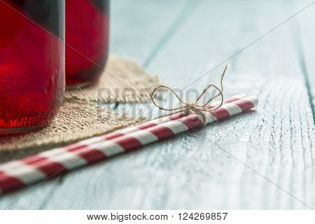 Closeup of two jars with organic raspberry juice placed on a burlap coasters next to two striped red and white drinking straws tied together with a twine bow placed on wooden boards surface